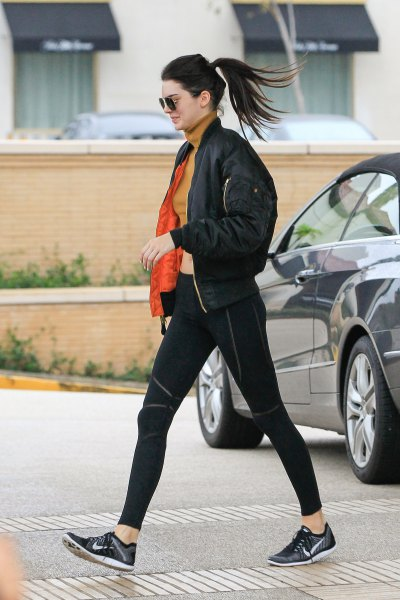black bomber jacket with orange mock-neck sweater