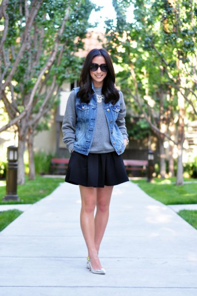 blue denim vest with gray crew-neck sweatshirt and black skater skirt