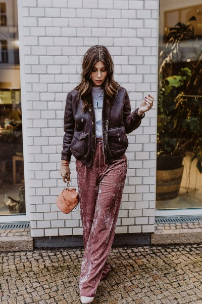black leather jacket with gray printed t-shirt and pink velvet pants with wide legs