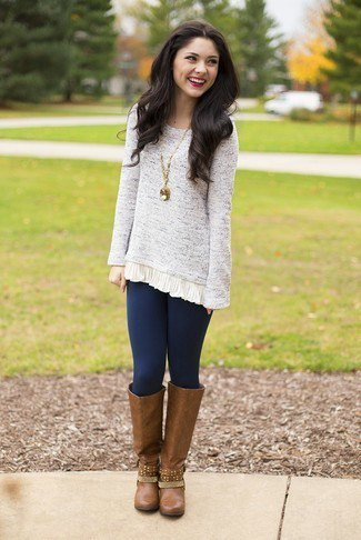 Light mottled tunic sweater with dark blue leggings and brown leather boots