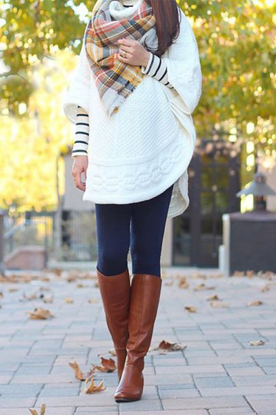 white tunic sweater with wide sleeves and knee-high boots made of brown leather