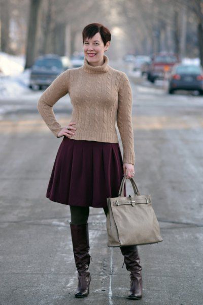 figure-hugging green turtleneck sweater with black pleated skirt and brown tights