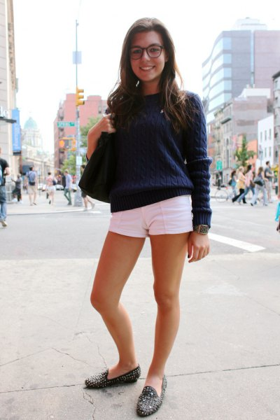 Dark blue knit sweater with white mini shorts and black loafers with spikes