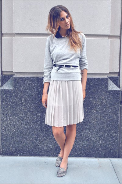 gray sweater with a relaxed fit and knee-length pleated skirt and silver loafers with spikes