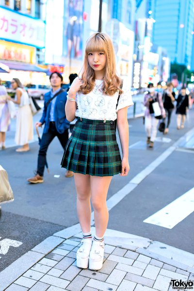 white graphic t-shirt with green and black checkered mini pleated skirt