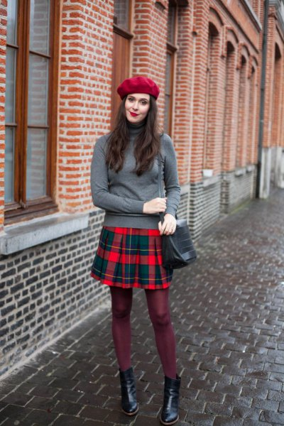 gray sweater with stand-up collar and red and blue checkered pleated skirt
