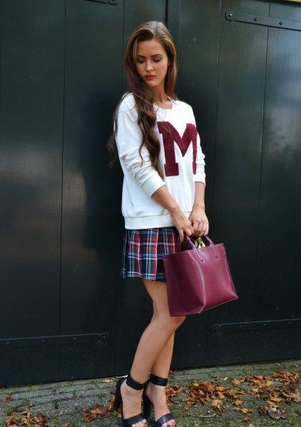 white graphic sweatshirt with dark blue checkered pleated mini skirt