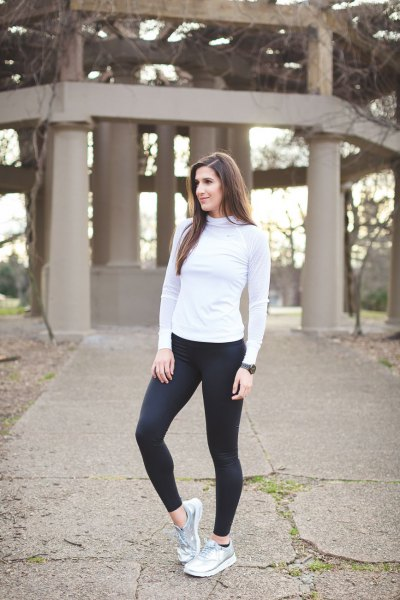 Light gray long-sleeved t-shirt with mock neck, black running trousers and silver sneakers