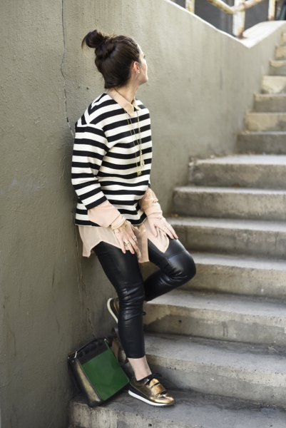 black and white striped long-sleeved sweater with leather pants and bronze-colored metallic sneakers