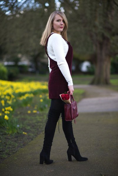 white sweater with black cord dress and black high-heeled boots
