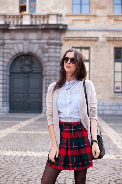 light blue shirt with buttons, gray cardigan and black checkered mini skirt