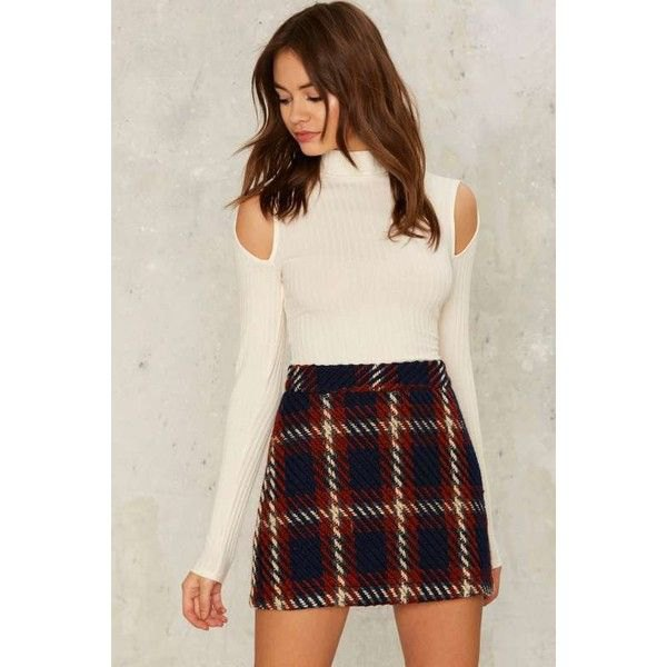 white, ribbed sweater with cold shoulder distance and black mini skirt made of checkered wool