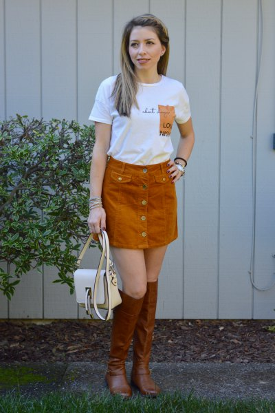 white printed t-shirt with green cord skirt and brown boots