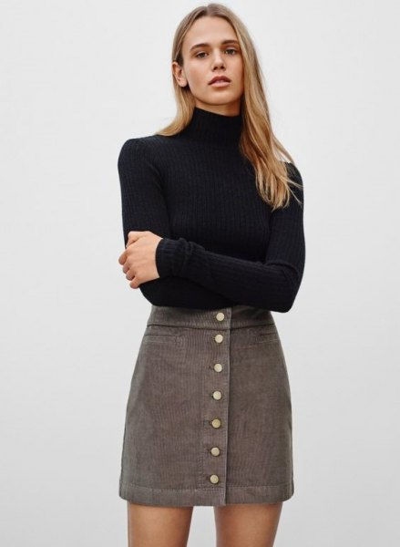 black, figure-hugging sweater with stand-up collar and gray, high-waisted mini cord skirt
