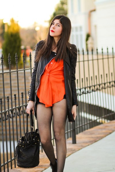 black leather jacket with orange blouse and mini shorts