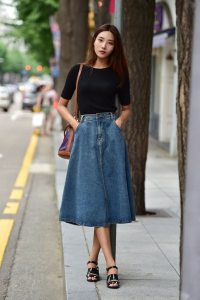 black short-sleeved T-shirt with a long denim skirt and long sandals