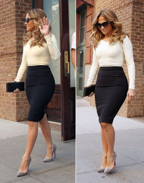 white figure-hugging sweater with black, form-fitting midi skirt with high waist