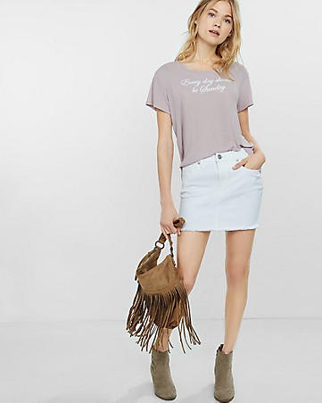pink graphic t-shirt with white mini skirt and suede boots
