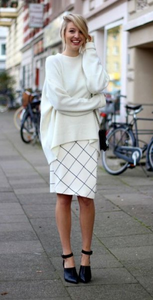 white, rough knitted sweater with round neck and checkered, knee-length skirt