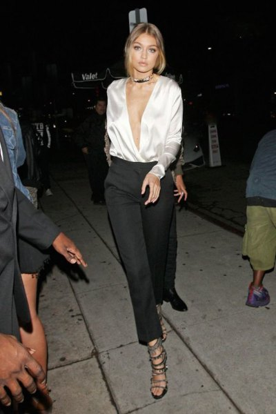 white silk blouse with deep v-neck and black chinos with wide legs