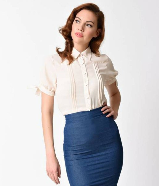 cream-colored shirt with a narrow collar and dark blue, figure-hugging midi skirt