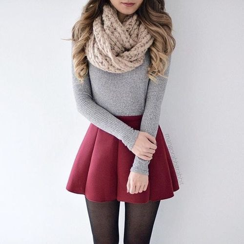 Cable knit scarf with a figure-hugging gray sweater and maroon pleated mini skirt