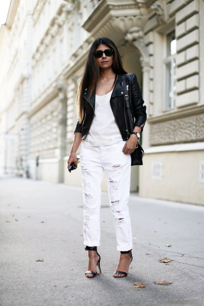 black leather moto jacket with white tank top and straight leg jeans and cuff
