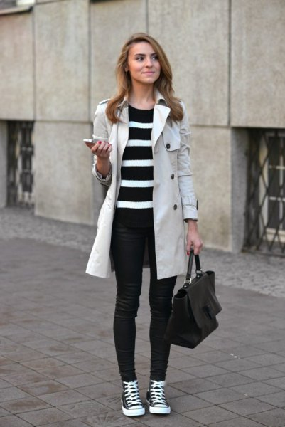 light gray longline coat with black and white striped tunic sweater and jeans