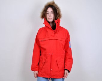 red windbreaker with hood made of faux fur and light blue jeans