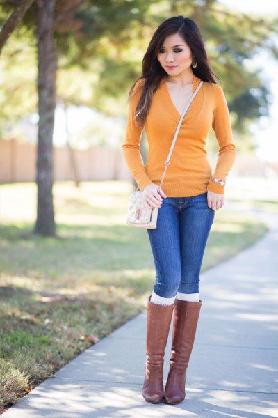 V-neck sweater, blue jeans and gray knee-high boots