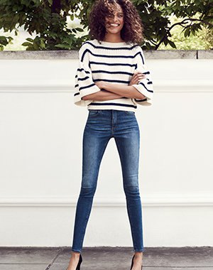 white and black striped sweater with wide sleeve and blue low skinny jeans