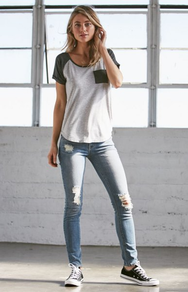 gray and white t-shirt with gray skinny low waist ripped jeans