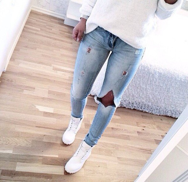 white casual fit knit sweater with light blue ripped jeans and boots