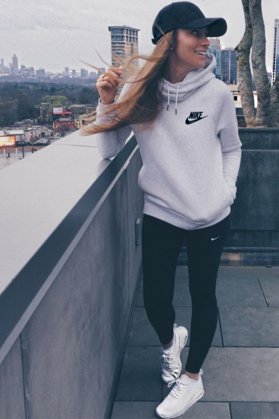 light gray hoodie with black skinny jeans and baseball cap