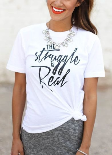 white graphic tee with silver necklace and heather gray skirt
