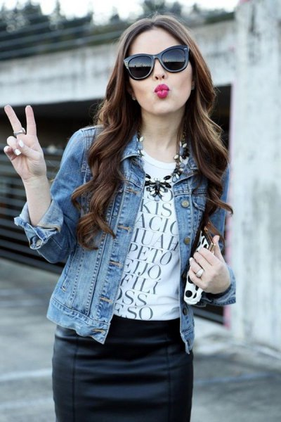 blue denim jacket with white graphic tee and black leather skirt