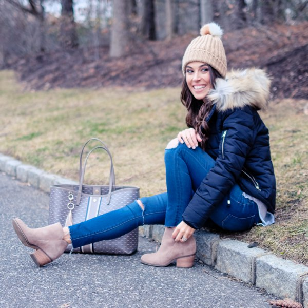 black down jacket with blue skinny ripped jeans and crepe knit hat