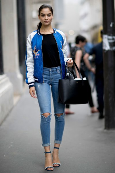 blue and white embroidered bomber jacket with black tee and ripped jeans