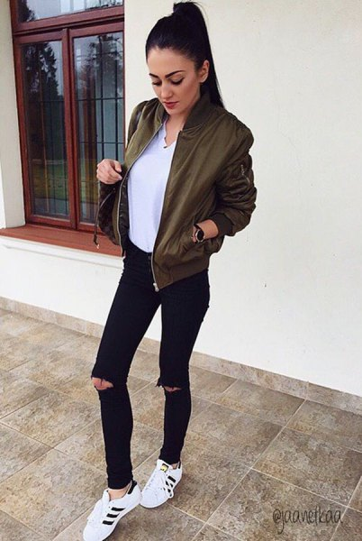 olive bomber jacket with white v-neck blouse and black ripped jeans