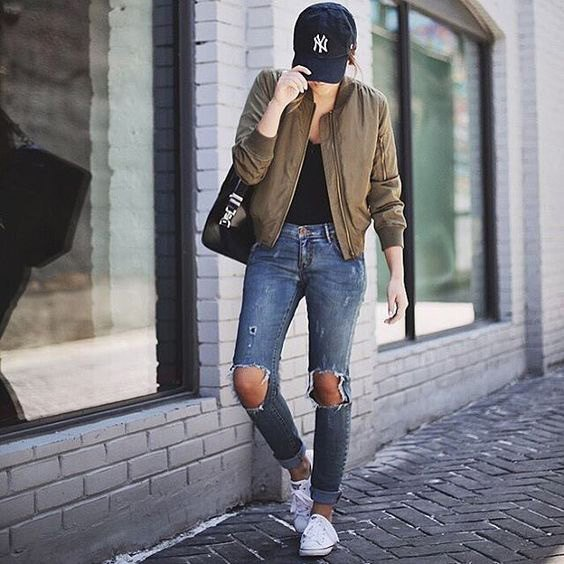 green bomber jacket with black scoop neck top and heavily ripped jeans