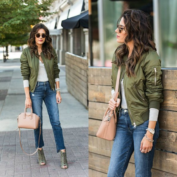 green flying jacket with gray long-sleeved tee and cropped jeans