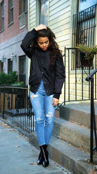 black jacket with blue high-ripped ripped skinny jeans and leather boots