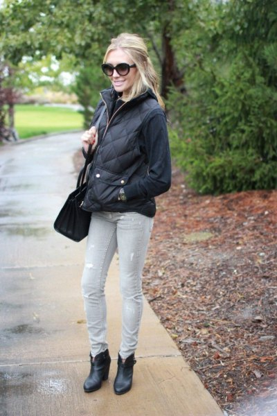 black sweater with quilted puffer jacket and light gray jeans