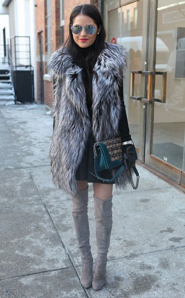 gray long faux fur vest with black sweater dress and high thigh boots