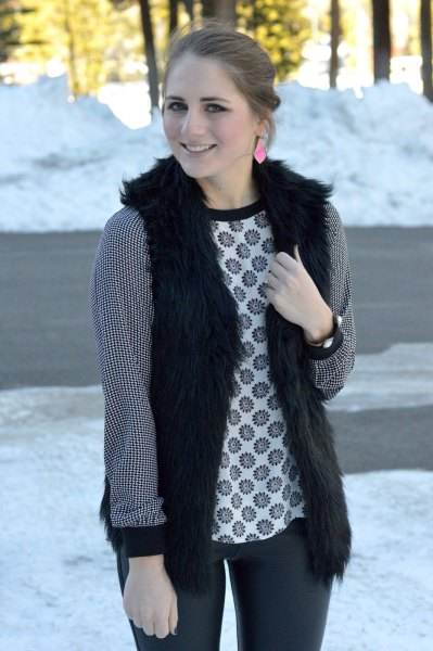 black vest with stem printed long sleeve top and dark gray jeans