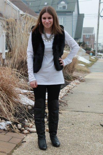 white long sleeve tunic top with black jeans and knee-high boots in leather