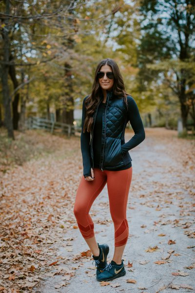 black leather vest with fitted sweater and green cropped leggings