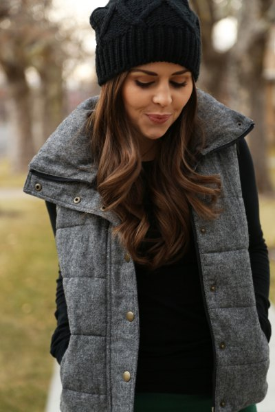 black knitted hat with gray quilted long vest and knitted sweater