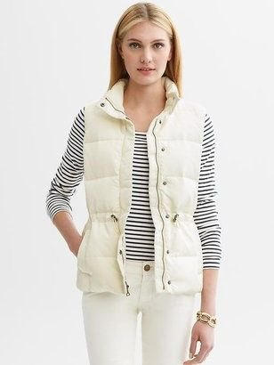 white down vest with striped t-shirt and slim jeans
