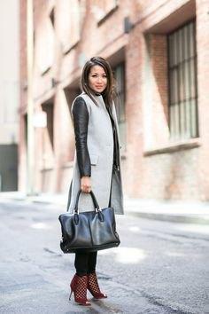 gray mid-length wool sleeveless jacket over black leather jacket